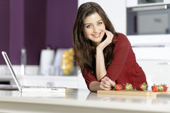 Woman in kitchen reading recipe Stock Image