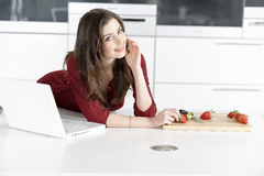 Woman in kitchen reading recipe Royalty Free Stock Photo