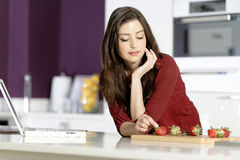 Woman in kitchen reading recipe Royalty Free Stock Photography