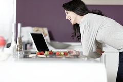 Woman in kitchen reading recipe Stock Photography
