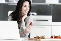 Woman in kitchen reading recipe Stock Images