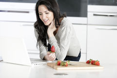 Woman in kitchen reading recipe Royalty Free Stock Image