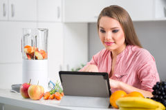 Woman in kitchen reading a recipe from a digital tablet Stock Photography