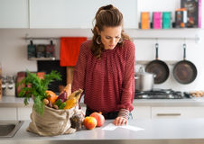 Woman in kitchen reading shopping list on counter with shopping Royalty Free Stock Photography