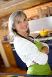 Woman in kitchen ready to cook Stock Image