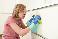 Woman on kitchen with rubber  washing gloves cloth and detergent cleaning bored and tired Royalty Free Stock Images