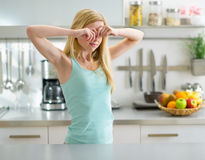Woman in in kitchen and rubbing eyes. Young woman standing in in kitchen and rubbing eyes after sleep Stock Photography