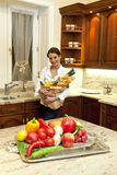 Woman in the kitchen with shopping bag Stock Photography