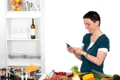 Woman in the kitchen with smartphone Royalty Free Stock Images