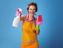 Woman with kitchen sponge showing bottle of detergent on blue Royalty Free Stock Photo