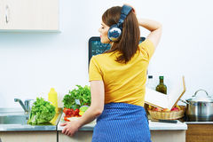 Woman in kitchen standing back. Girl cooking Stock Photos