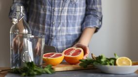 Woman in the kitchen at the table. Closeup of a woman cutting a knife ripe red delicious grapefruit on a wooden Board in the kitchen stock footage