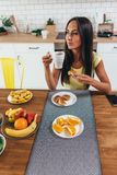 Woman at the kitchen table having breakfast with coffee croissants and fruits.  stock photos
