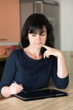 Woman in the kitchen with tablet Royalty Free Stock Image