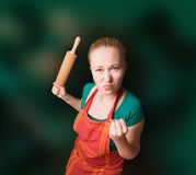 Woman with kitchen tool (rolling pin) Royalty Free Stock Image
