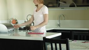 The woman in the kitchen uses the tablet, just woke up. Breakfast. Early morning. A young woman with blond hair and a pink shirt is sitting in a dark kitchen stock video footage