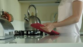 The woman in the kitchen uses the tablet, just woke up. Breakfast. Early morning. A young woman with blond hair and a pink shirt is standing in a dark kitchen stock footage