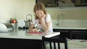 The woman in the kitchen uses the tablet, just woke up. Breakfast. Early morning. A young woman with blond hair and a pink shirt is sitting in a dark kitchen stock footage
