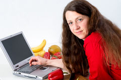Woman in the kitchen using computer Stock Photos