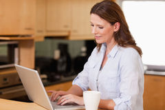 Woman in the kitchen using her laptop Stock Images