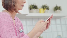 Woman in the kitchen using smartphone. Profile. Attractive woman at home using smartphone in kitchen sending message on social media sharing and connecting stock footage