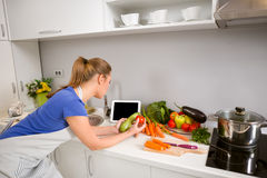 Woman in kitchen using tablet Stock Photography