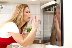 Woman in a kitchen waiting with anxiety. Caucasian woman in a kitchen waiting with anxiety in front of the oven Stock Images