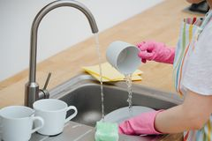 Woman in a kitchen is washing cups and dishes. Close up. stock images