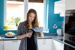 Woman in kitchen woman pouring a glass of water. Young blonde woman in kitchen woman pouring a glass of water. Standing in a bright modern kitchen. Dressed in a Royalty Free Stock Image