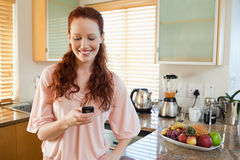 Woman in the kitchen writing text message Stock Photo