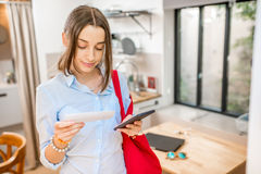 Woman in the kitchen. Young woman standing with shopping list and smartphone in the kitchen Royalty Free Stock Photo