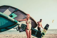 Woman kitesurfer enjoying summertime on sandy beach with her boyfriend. Pretty smiling Caucasian women kitesurfer enjoying summertime on sandy beach with her Royalty Free Stock Photography