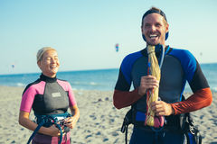Woman kitesurfer enjoying summertime on sandy beach with her boyfriend. Pretty smiling Caucasian women kitesurfer enjoying summertime on sandy beach with her Royalty Free Stock Images