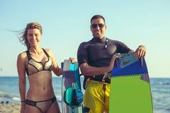 Woman kitesurfer enjoying summertime on sandy beach with her boyfriend. Pretty smiling Caucasian women kitesurfer enjoying summertime on sandy beach with her Stock Photos