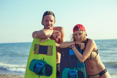 Woman kitesurfer enjoying summertime on sandy beach with her boyfriend. Pretty smiling Caucasian women kitesurfer enjoying summertime on sandy beach with her Stock Image