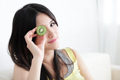 Woman with kiwi slices in front of eyes Royalty Free Stock Photo