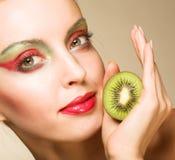 Woman with kiwi on white Stock Photo