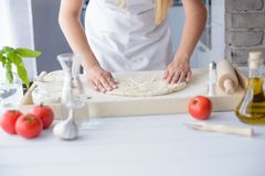 Woman kneading pizza dough on wooden pastry board. Stock Photo