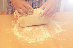A woman kneads a homemade dough for pizza production. Royalty Free Stock Photos