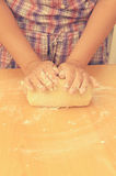A woman kneads a homemade dough for pizza production. Stock Images
