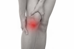 Woman with knee feeling pain on white background. Royalty Free Stock Photography