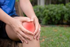 Woman with knee pain, arthrosis of the knee. In the garden stock photos