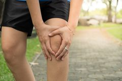 Woman with knee pain, arthrosis of the knee. In the garden stock photo