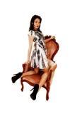 Woman kneeling in armchair. Stock Image