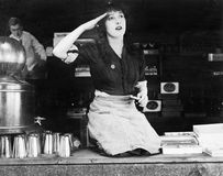 Woman kneeling on the counter of a bar and saluting. (All persons depicted are no longer living and no estate exists. Supplier grants that there will be no Royalty Free Stock Photos
