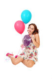 Woman kneeling on floor with balloons. A beautiful young woman kneeling on the floor holding two balloons and Royalty Free Stock Image