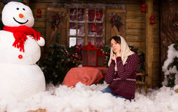 Woman Kneeling on Floor with Cottons Near Snow Man Stock Photos