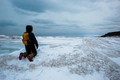 Woman kneeling on frozen wave looking into the distance royalty free stock images