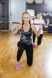 Woman Kneeling While Lifting Barbell In Gym Stock Images