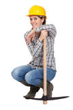 Woman kneeling by a pickax Royalty Free Stock Image